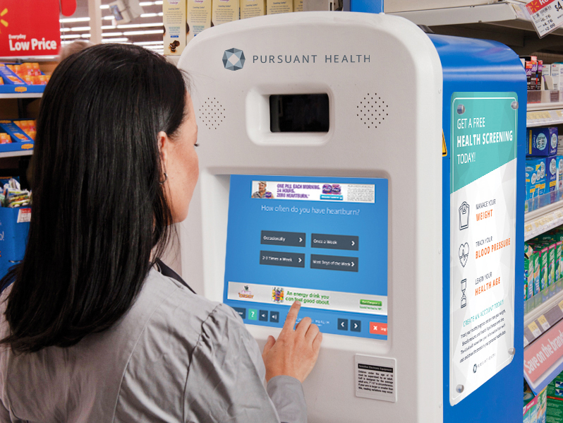 Woman Sitting at Kiosk in Walmart Pharmacy Selecting an Option on the Touch Screen Interface
